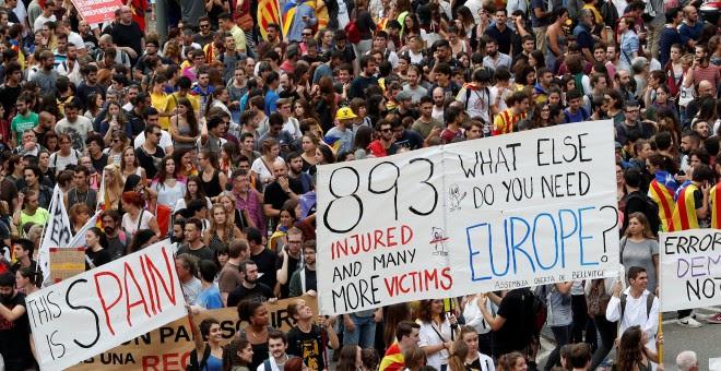 Participantes en la manifestación en protesta por la actuación policial portan carteles pidiendo ayuda a la Unión Europea, en Barcelona, este martes. REUTERS/Yves Herman