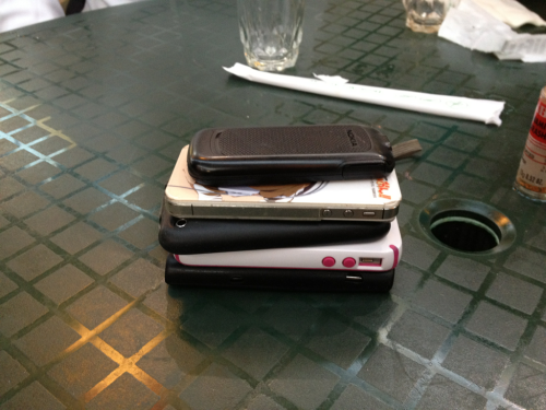 """Introducing our new game called: """"Don't Be A Di*k During Meals With Friends."""" The first person to crack and look at their phone picks up the check. Our (initial) purpose of the game was to get everyone off the phones free from twitter/fb/texting and to encourage conversations. Rules: 1) The game starts after everyone has ordered. 2) Everybody places their phone on the table face down. 3) The first person to flip over their phone loses the game. 4) Loser of the game pays for the bill. 5) If the bill comes before anyone has flipped over their phone everybody is declared a winner and pays for their own meal. Variations/house rules: -Starting the game after everyone is seated. -In the rare event that multiple people flip their phones simultaneously, the bill is split between said players. - Feel free to invoke penalties/strikes systems. Notes: - No touching or messing with anybody else's phones. - You don't have to stack the phones. This was done for picture taking purposes. - I realize I should perhaps think of a different name for this awesome game. Because I don't mean to imply that everyone who checks their phone during meals is a di*k. - I recommend not being such a stickler or hardass on people about the rules and even initiation of the game. Basic premise is to just get people open to the idea of staying active and attentive to one another. But if someone has to take a call; they have to take a call =). - Have fun! It's really more of a fun concept in this new age high tech life of ours. Conversation is the spice of life."""
