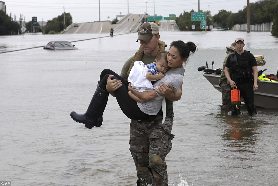 Houston Police SWAT officer Daryl Hudeck carries Catherine Pham and her 13-month-old son Aiden to safety after rescuing them from their home