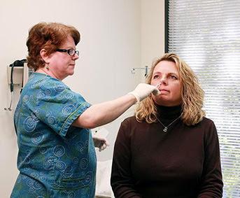 Woman receiving flu vaccine nasal mist from nurse