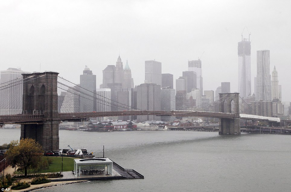 Eerie skies: Rain and wind pass over the Brooklyn Bridge and the New York skyline as Hurricane Sandy advances on the city on Monday