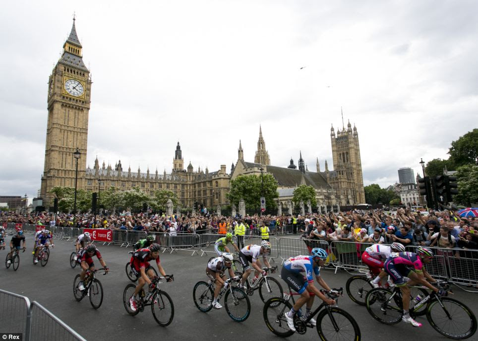 Go on! Crowds cheer as cyclists pass through Parliament Square as they near the end of the race's third stage