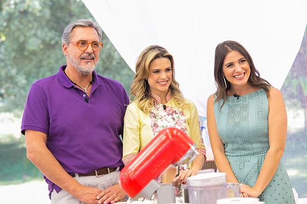 Os jurados Fabrizio Fasano Jr. e Beca Milano, sorriem ao lado da apresentadora do Júnior Bake Off, Carol Fiorentino
