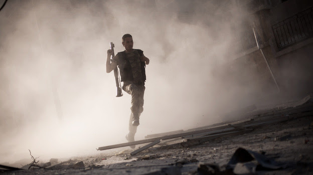 A Free Syrian Army fighter runs after attacking a tank with a rocket-propelled grenade during fighting in Aleppo, Syria, in September 2012. The rebels say they are willing to take on the Islamic State, but need more weapons. (AP)