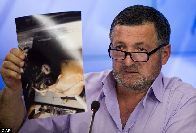 Gruesome: The father showed images of his son's bullet-riddled body laying in a Florida morgue