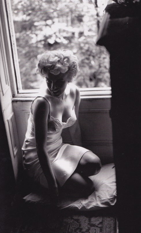 Marilyn Monroe in a slip, looking out window