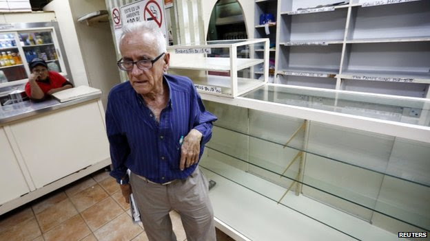 A man reacts after he found all shelves empty at a bakery in Caracas on 14 January, 2014
