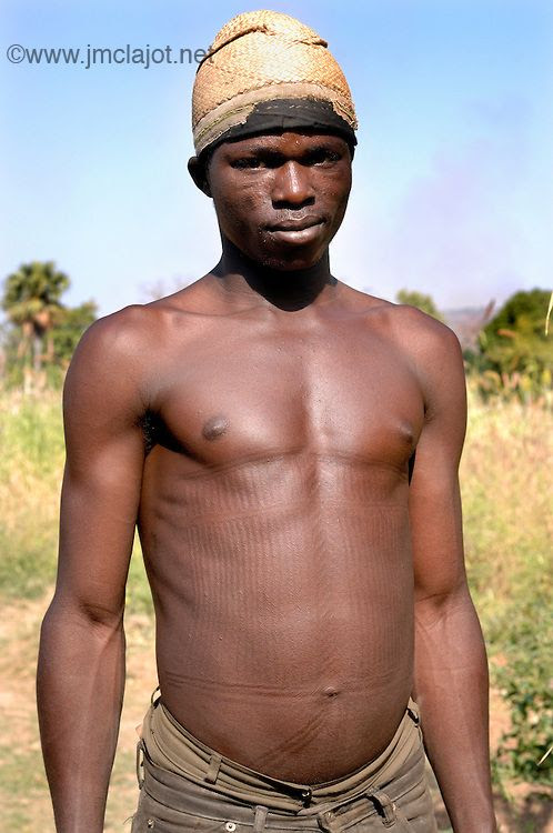 Africa | Man with tribal scarification on his face and body. Scarification is used as a form of initiation into adulthood, beauty and a sign of a village, tribe, and clan. Natitingou, Benin | © Jean-Michel Clajot