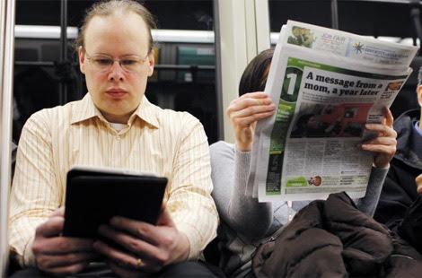 Un lector de libro electrónico junto a otro de papel.   Reuters