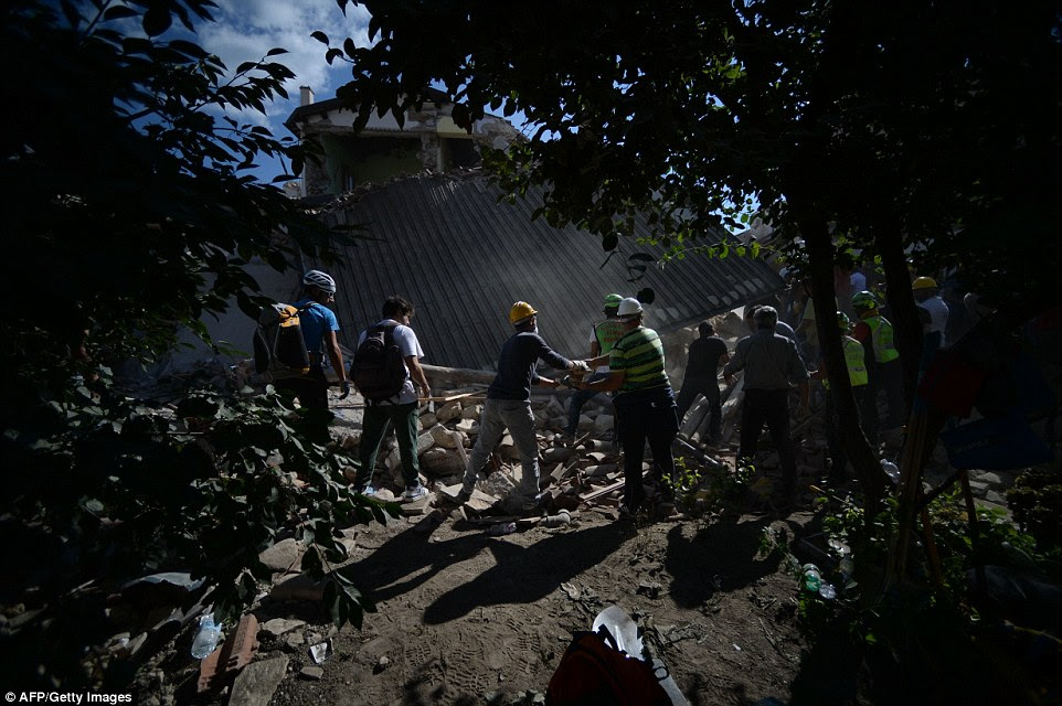 Volunteers assist rescue emergency service personnel in front of a damaged house in the central Italian village of Amatrice