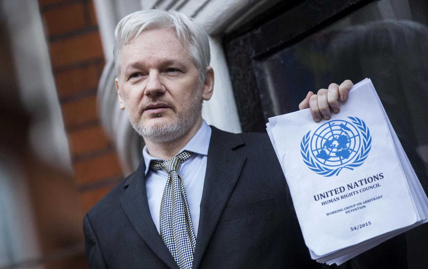 Julian Assange holds UN report on balcony.