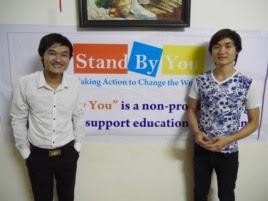 Phạm Minh Dap (trái) và em trai đứng trước một tấm băng rôn quảng cáo lớp học ngoại ngữ miễn phí Stand By You cho học sinh, sinh viên nghèo (Marianne Brown/VOA)