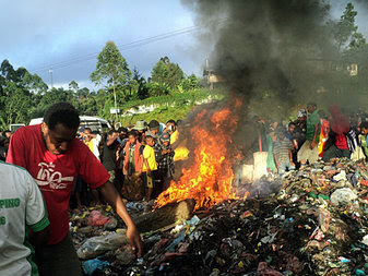 Bystanders, including children, watching as a woman accused of witchcraft is burned alive in Papua New Guinea, earlier this month.
