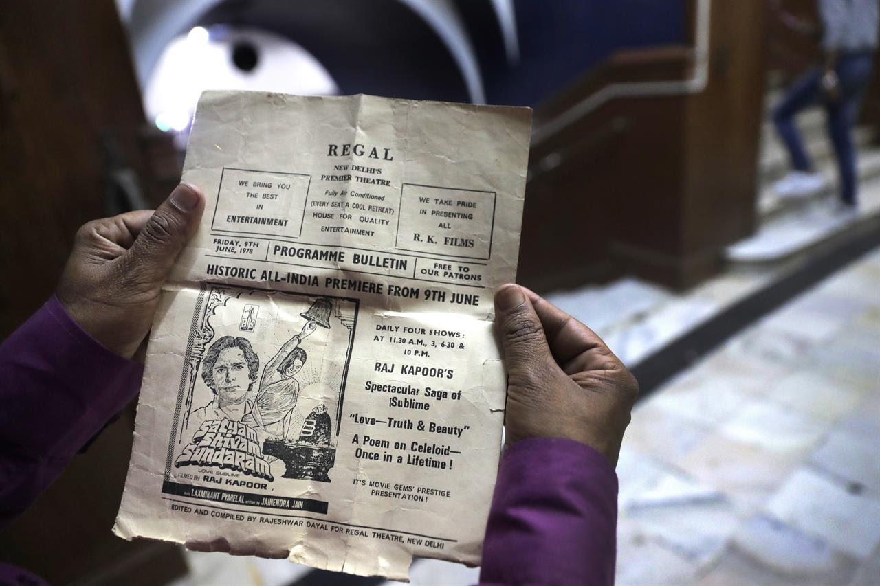 In this Friday, March 31, 2017 photo, a movie lover shows an an old 1978 program bulletin of Regal Theater at the theater in New Delhi, India. From Bollywood superstars to political heavyweights, the Regal theater had hosted some of India's biggest names over more than eight decades. But with nostalgic theater-goers singing their way to the exits after a final showing of a Bollywood classic, the iconic New Delhi theater has closed its doors to make way for a multiplex.