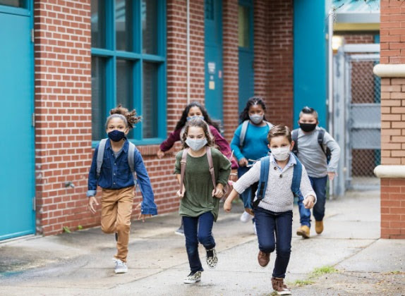 Group of children running outside with masks on