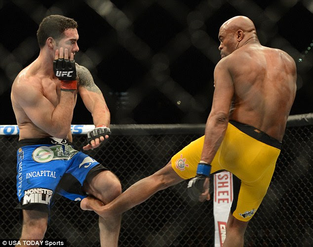 Horrific: This is the moment Chris Weidman, left, broke Anderson Silva's leg when he blocked Silva's kick with his knee. Experts fear the injury could end Silva's career