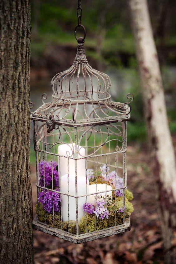 ein vintage Vogelkäfig mit Moos und lila und lila Blüten können angehalten werden, über die Rezeption