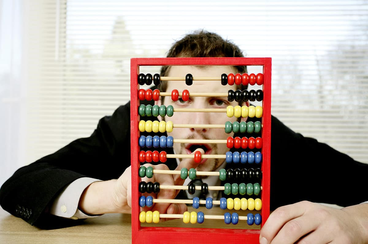 Man planning his financial goals with an abacus