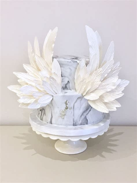 Angel wings cake on a grey and silver marbled fondant. The