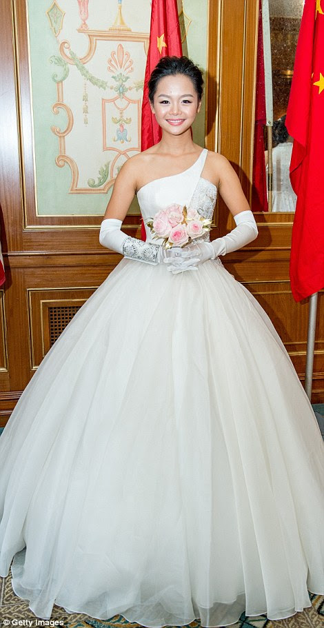 A young debutante poses in a gown