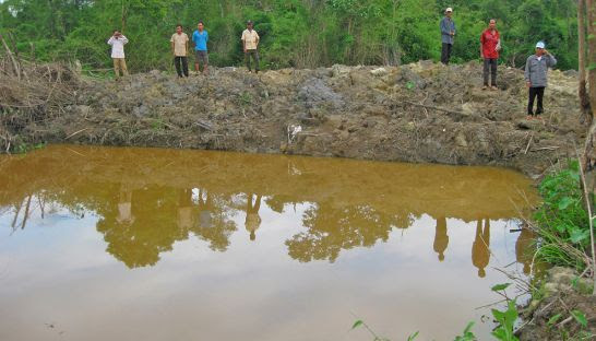 People inspect a pond last month that was allegedly constructed by Vietnamese in Ratanakkiri province.