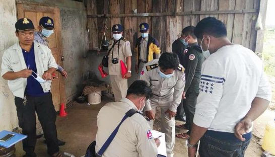 Police investigate a crime scene yesterday where a young child was murdered in Battambang province. Photo supplied