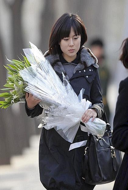 Una ragazza porta un mazzo di fiori all'ambasciata nord coreana di Pechino
