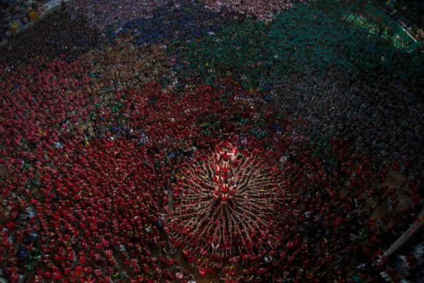 Members of the Castellers Joves Xiquets de Valls try to complete their human tower during the 25th Human Tower Competition in Tarragona, Spain, on Sunday, Oct. 5, 2014. The tradition of building human towers, or castells, dates back to the 18th century and takes place during festivals in Catalonia, where colles, or teams, compete to build the tallest and most complicated towers. The structure of the castells varies depending on their complexity. A castell is considered completely successful when it is loaded and unloaded without falling apart. The highest castell in history was a 10 floor structure with 3 people in each floor. In 2010 castells were declared by UNESCO one of the Masterpieces of the Oral and Intangible Heritage of Humanity.