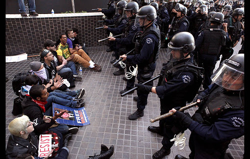 Occupy L.A. protesters sit with locked arms in front of a wave of approaching riot police during a protest in front of the Bank of America on Hope Street and 3rd Street. (Arkasha Stevenson/Los Angeles Times) by Pan-African News Wire File Photos