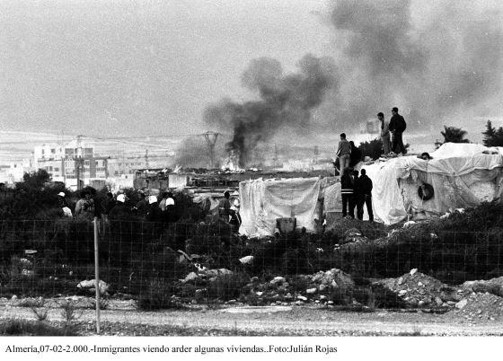 Un grupo de inmigrantes magrebíes observa cómo arden algunas chabolas en El Ejido (Almería), en 2000.