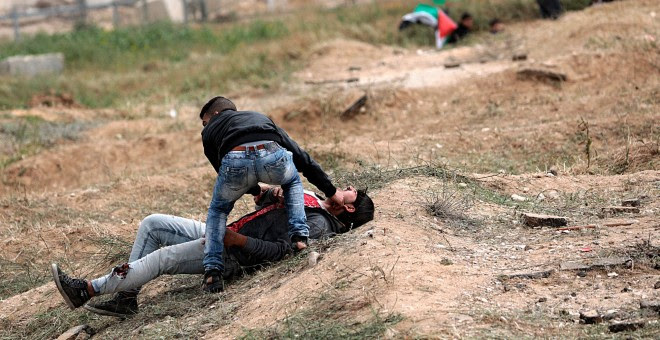 Un palestino ayuda a un compañero herido durante los enfrentamientos con soldados israelíes en el este de Beit Hanun, norte de la Franja de Gaza.-  EFE/Mohammed Saber
