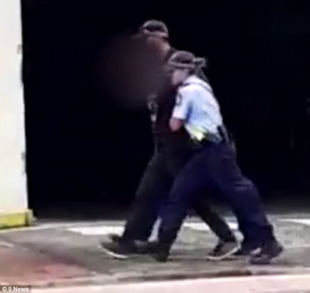 A man was seen being escorted from the scene in handcuffs by police shortly after incident
