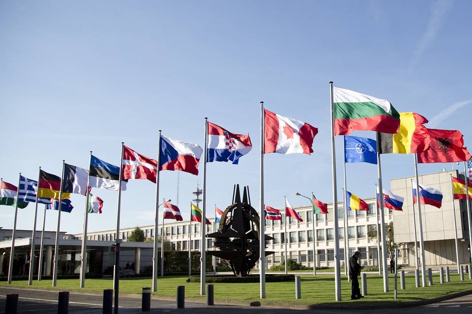 Flags of member countries in front of NATO headquarters in Brussels.