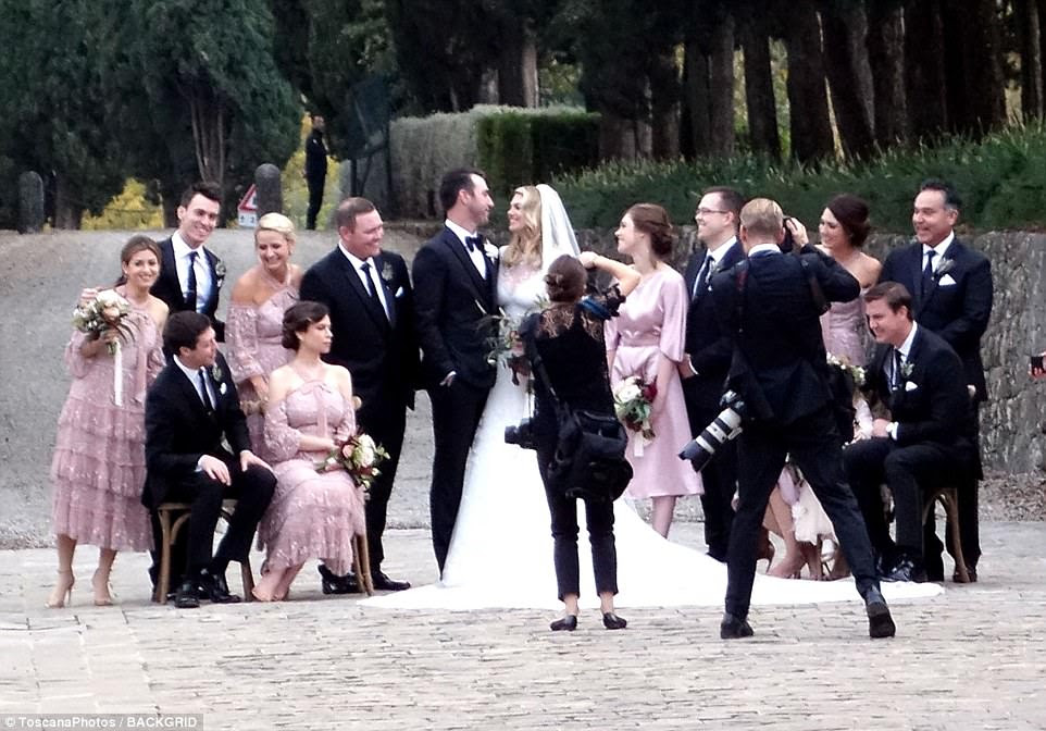 Time for photos: The bride and groom were surrounded by the wedding party, which included bridesmaids in pink