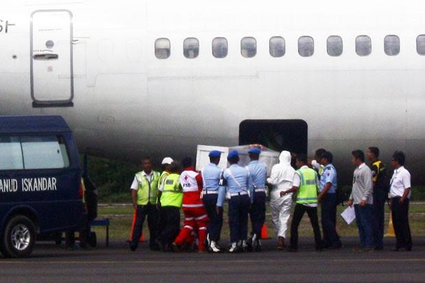 Equipes de resgate da Malásia colocam caixão com corpo de vítima de queda do avião da AirAsia em aeronave nesta terça-feira (27), último dia das operações de busca (Foto: Yudha Manx/AFP)