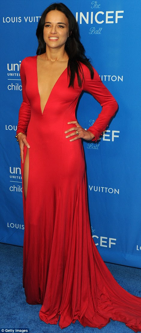 Skintight scarlet: Michelle Rodriguez was also feeling risque in a plunging and slit-to-the-thigh dress