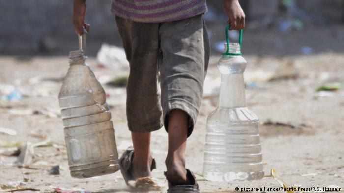 Menino paquistanês carrega dois galões com água