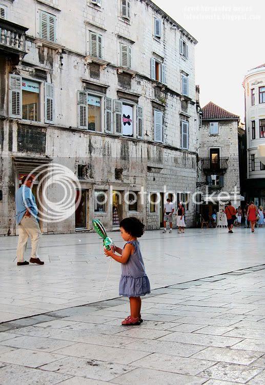 Una niña con un globo en las manos en las calles de Split