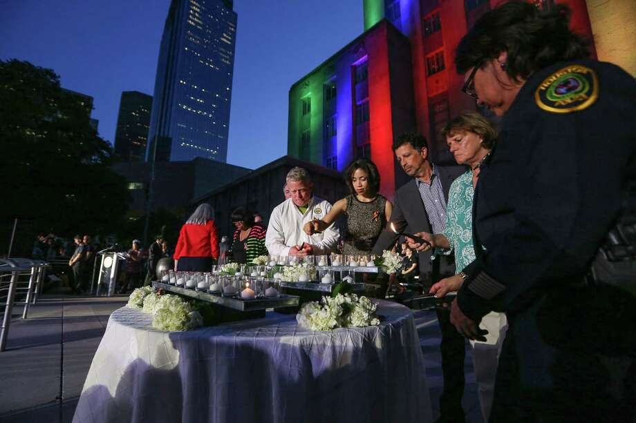 Officials at a Houston vigil on Wednesday lights candles in honor of the victims of the Orlando shooting. Photo: Steve Gonzales, Houston Chronicle / © 2016 Houston Chronicle