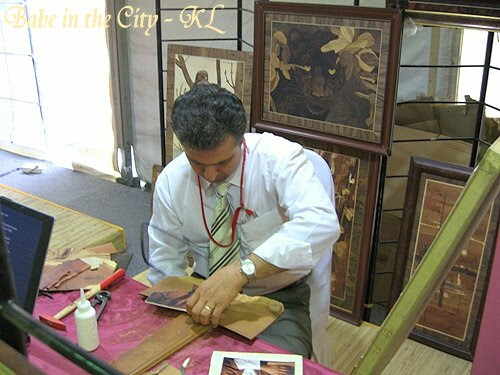 Mr Mehran from Iran showing his Inlay skills. He's sawing the wood piece to fit into the painting.