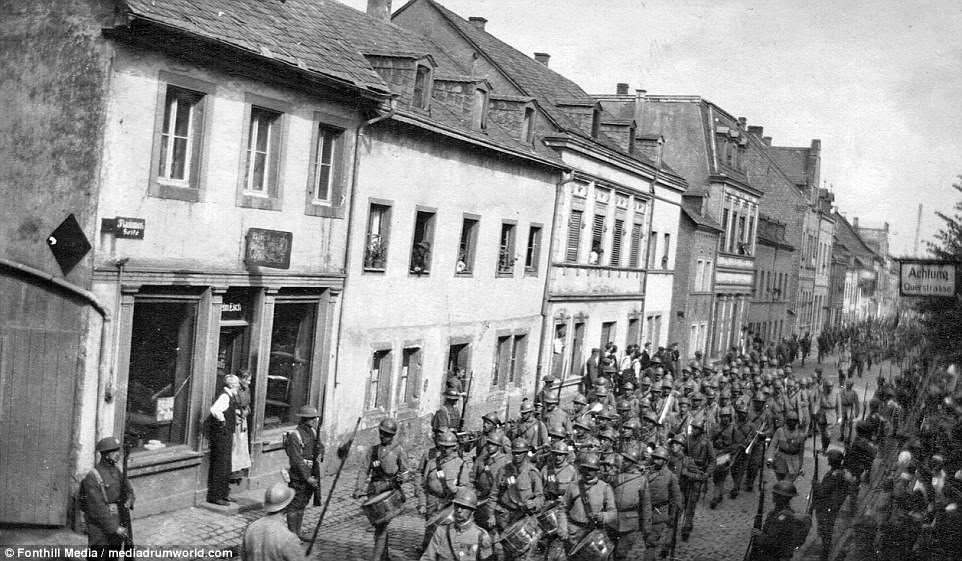A parade of French troops on the street, which seems to be lined with British soldiers. Foley states that it is important to have some level of understanding of the situation in Germany that the men of the occupation forces found themselves having to deal with