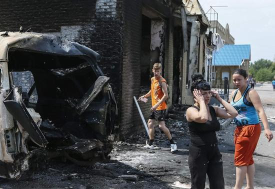 Local residents react as they stand near destroyed houses and vehicles after what locals say was overnight shelling by Ukrainian forces, in the eastern Ukrainian town of Slaviansk June 9, 2014.  REUTERS-Gleb Garanich