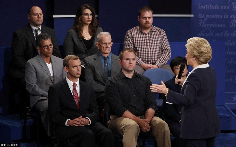 Membros do público olhar sobre Hillary Clinton fala com eles e responde a uma pergunta durante o segundo debate presidencial