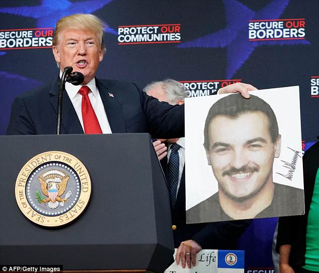 President Donald Trump has prompted fury among some after he signed photographs of young victims killed by undocumented immigrants. He is pictured above holding a portrait ofRonald da Silva