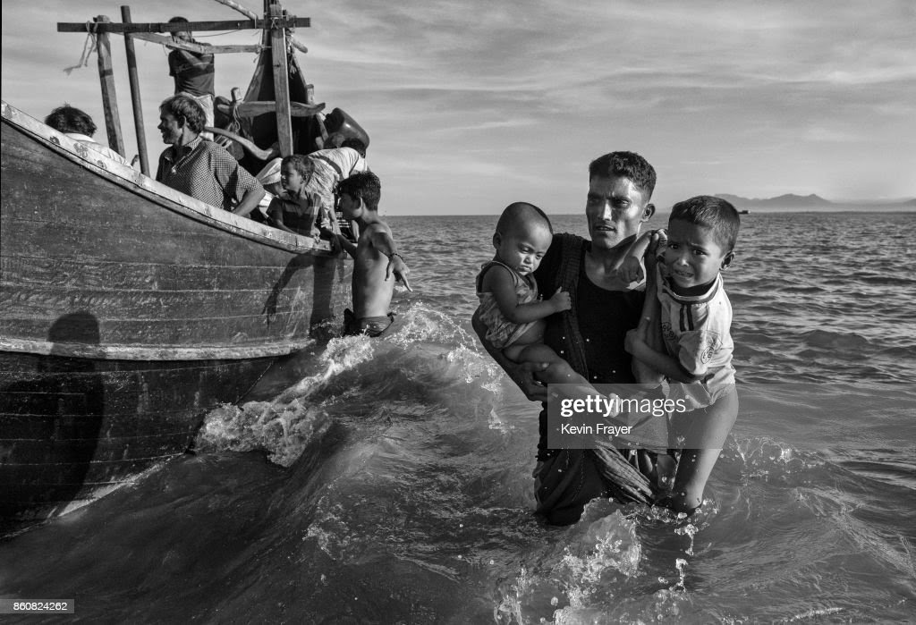 COX'S BAZAR, BANGLADESH - OCTOBER 01: Rohingya refugee children are carried from a boat at a beach on the Bangladesh side of the Naf River at Shah Porir Dwip after fleeing their village in Myanmar, on October 1, 2017 in Cox's Bazar, Bangladesh. More than half a million Rohingya refugees have flooded into Bangladesh to flee an offensive by Myanmar's military that the United Nations has called 'a textbook example of ethnic cleansing'. The refugee population is expected to swell further, with thousands more Rohingya Muslims said to be making the perilous journey on foot toward the border, or paying smugglers to take them across by water in wooden boats. Hundreds are known to have died trying to escape, and survivors arrive with horrifying accounts of villages burned, women raped, and scores killed in the 'clearance operations' by Myanmar's army and Buddhist mobs that were sparked by militant attacks on security posts in Rakhine state on August 25, 2017. What the Rohingya refugees flee to is a different kind of suffering in sprawling makeshift camps rife with fears of malnutrition, cholera, and other diseases. Aid organizations are struggling to keep pace with the scale of need and the staggering number of them - an estimated 60 percent - who are children arriving alone. Bangladesh, whose acceptance of the refugees has been praised by humanitarian officials for saving lives, has urged the creation of an internationally-recognized 'safe zone' where refugees can return, though Rohingya Muslims have long been persecuted in predominantly Buddhist Myanmar. World leaders are still debating how to confront the country and its de facto leader, Aung San Suu Kyi, a Nobel Peace Prize laureate who championed democracy, but now appears unable or unwilling to stop the army's brutal crackdown.