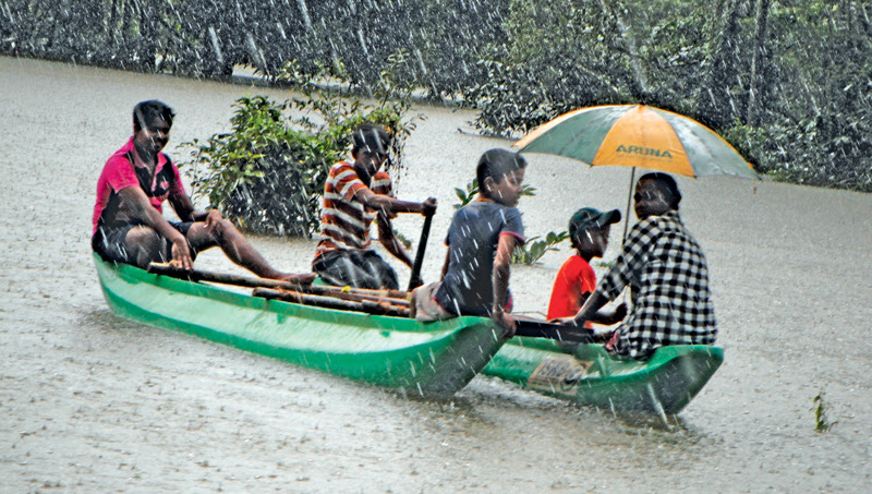 The opening of the sluice gates of the Kukule Ganga reservoir following heavy rains during the last few days has submerged several low lying areas in the Kosgulana Malkawa, Paragoda Dambala, Bulathsinhala and Madurawela DS Divisions. Here, a group of affected people moving to safer areas by boat. Picture by Saman D Withana in Palindanuwara