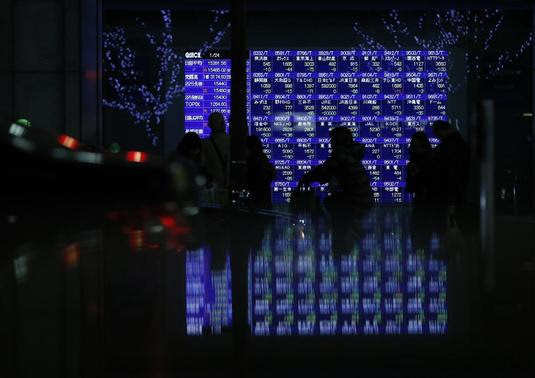 Pedestrians walk past an electronic board showing various stock prices, which are reflected in a polished stone surface, outside a brokerage in Tokyo January 24, 2014. REUTERS-Yuya Shino