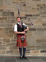 Seorang lelaki Scotland dengan pakaian tradisional sedang memainkan bag paip