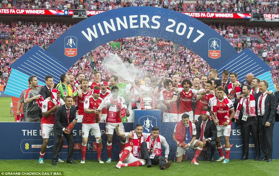 The Arsenal squad and staff cheers and spray champagne as they savour victory in the last game of the season