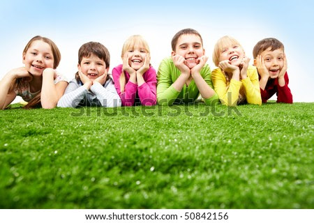 stock photo : Image of happy boys and girls lying on a green grass